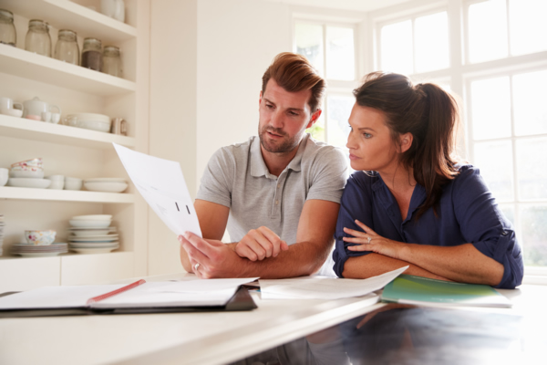 A young couple reviewing their financial plan in the kitchen.