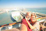 Photo of an elderly couple taking a selfie in front of a cruise ship.