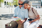 Photo of an elderly couple sitting on a bench and reviewing a map.