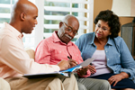 Photo of a younger black man reviewing documents with an elderly black couple.
