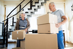 Photo of an elderly couple packing up moving boxes.