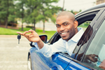 Photo of a smiling young black male leaning out of the driver's side window holding his car keys.